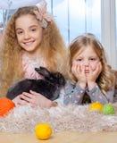Belles petites filles se trouvant sur le tapis et jouant avec le lapin Images stock