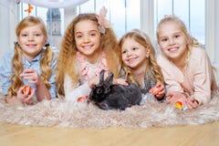 Belles petites filles se trouvant sur le tapis et jouant avec le lapin mignon Image stock