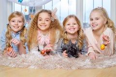 Belles petites filles se trouvant sur le tapis et jouant avec le lapin mignon Image libre de droits
