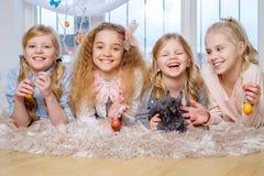 Belles petites filles se trouvant sur le tapis et jouant avec le lapin mignon Photos stock