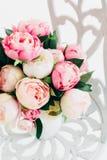Belles pivoines de bouquet sur la chaise forgée de vintage dans la chambre blanche photographie stock