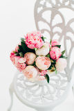 Belles pivoines de bouquet sur la chaise forgée de vintage dans la chambre blanche images stock