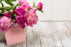 Belles pivoines de fleurs dans le panier sur le fond en bois clair L'espace pour le texte Photographie stock