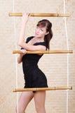 Belles poses de femme retenant l'échelle de corde en bambou. Photographie stock libre de droits