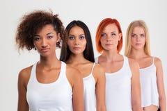 Belles quatre femmes se tenant dans une rangée Image stock
