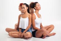 Belles quatre filles s'asseyant sur le plancher Photo stock