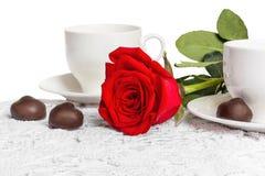 Belles rose de rouge et tasse de thé chaud avec du chocolat Images stock
