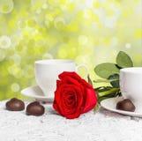 Belles rose de rouge et tasse de thé chaud avec du chocolat Photo libre de droits