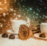 Belles rose de rouge et tasse de thé chaud avec du chocolat Photo stock