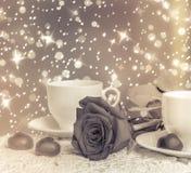 Belles rose de rouge et tasse de thé chaud avec du chocolat Photographie stock