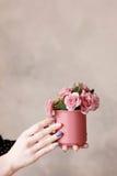 Belles roses dans la tasse cramoisie se tenant dans des mains Photographie stock libre de droits