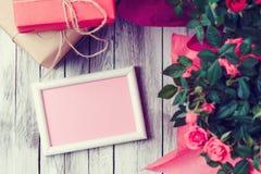 Belles roses dans un pot avec une carte de voeux vierge sur le fond en bois rustique blanc Images stock