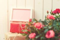 Belles roses dans un pot avec une carte de voeux vierge sur le fond en bois rustique blanc Photographie stock libre de droits