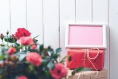 Belles roses dans un pot avec une carte de voeux vierge sur le fond en bois rustique blanc Images libres de droits