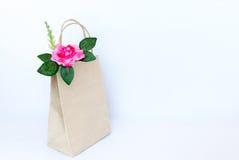 Belles roses roses dans le sac de papier brun d'isolement sur le b blanc Photographie stock libre de droits