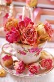 Belles roses sèches dans la tasse de thé de porcelaine Photos libres de droits