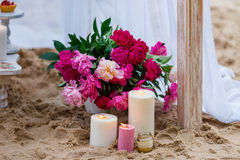 Belles, sensibles décorations de mariage avec des bougies et fleurs fraîches sur la plage Photo libre de droits