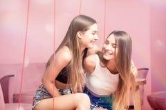 Belles soeurs de jumeaux souriant ensemble, moments heureux Image libre de droits