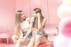 Belles soeurs de jumeaux souriant ensemble, moments heureux Photos libres de droits