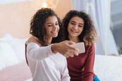 Belles soeurs posant pour le selfie à la maison Image libre de droits