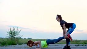 Belles, sportif, les jeunes femmes dans des lunettes de soleil, dans des collants, exécutent synchroniquement les exercices de fo banque de vidéos
