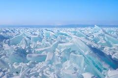 Belles transitoires bleues de glace sur le lac congelé avec des montagnes sur le fond photos libres de droits