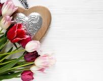 Belles tulipes colorées et grand coeur en bois sur la table en bois blanche Valentines, fond de ressort Moquerie florale  photos libres de droits