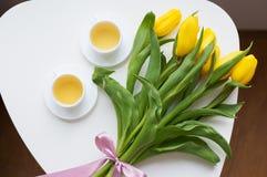 Belles tulipes jaunes, deux tasses de thé vert, ressort Photographie stock libre de droits