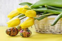 Belles tulipes jaunes en panier en osier et oeufs de pâques blancs Photos libres de droits