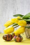 Belles tulipes jaunes en panier en osier et oeufs de pâques blancs Image stock