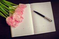 Belles tulipes roses avec un carnet Photos libres de droits