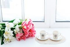 Belles tulipes rouges dans le vase et des deux tasses sur un filon-couche de fenêtre Photos libres de droits