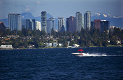 Bellevue WA Skyline Lake Washington. City of Bellevue from Lake Washington with Speed Boat and Snow Capped Mountains in Background Royalty Free Stock Image