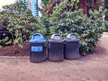 View of three trash cans, one specifically for recycling, in a park in the downtown city area of Bellevue