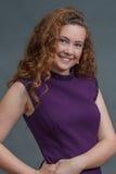 Belleza adolescente en el vestido púrpura que hace muecas a la derecha de la cámara Fotografía de archivo libre de regalías