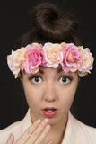 Belleza adolescente que lleva una corona floral con una expresión sorprendida Foto de archivo