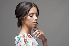 Belleza atractiva blanda con el finger en el peinado de la barbilla y del bollo que mira abajo Fotos de archivo libres de regalías