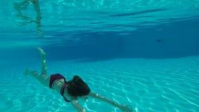 Belleza a cámara lenta con la mujer joven que nada bajo el agua en piscina almacen de video