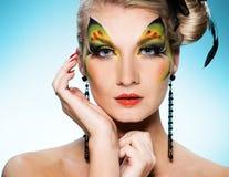 Belleza con arte de la cara de la mariposa Fotos de archivo libres de regalías