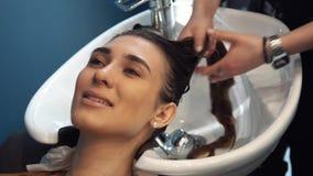 Belleza, cuidado del cabello y concepto de la gente - mujer joven feliz con la cabeza del lavado del peluquero en la peluquer?a almacen de video