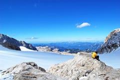 Belleza de la naturaleza, paisaje alpino que sorprende con las rocas, caminando en soporte, cielo azul, nubes, nieve, sol imagen de archivo