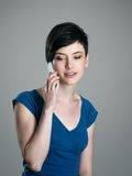 Belleza del pelo corto que habla en el teléfono móvil que mira abajo Imagenes de archivo
