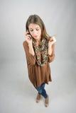 Belleza en cuestión pensativa en el teléfono móvil que mira abajo Imagen de archivo