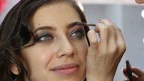 Belleza femenina Estilista del artista de maquillaje que se aplica con el cosmético del cepillo en la ceja de la mujer joven almacen de metraje de vídeo