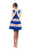Belleza femenina triste blanda en el vestido azul del verano que mira abajo con la cabeza en las manos Imágenes de archivo libres de regalías