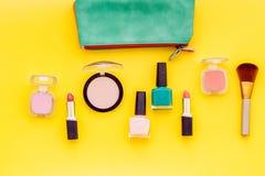 Belleza fijada con los cosméticos decorativos Esmalte de uñas, cepillos y bolso en maqueta amarilla y rosada de la opinión superi imagenes de archivo