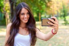 Belleza joven con el pelo marrón largo que mira smartphone Fotos de archivo