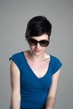 Belleza joven con las gafas de sol que miran abajo Imagen de archivo