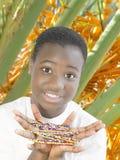 Belleza joven del Afro que juega con las perlas en un oasis Imagen de archivo
