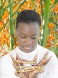 Belleza joven del Afro que juega con las perlas en un oasis Imágenes de archivo libres de regalías
